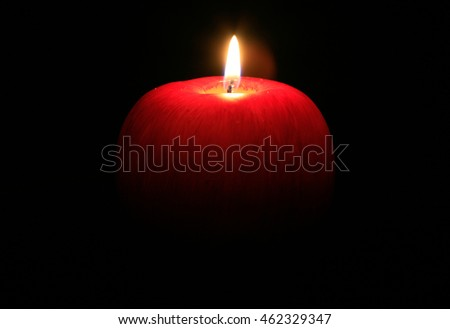A red wax apple candle burns in the darkness.