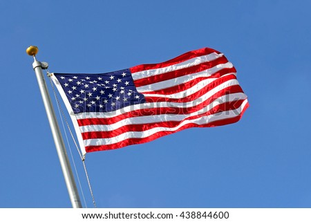 A red, white and blue American Flag is raised into the blue sky, blowing in the wind.