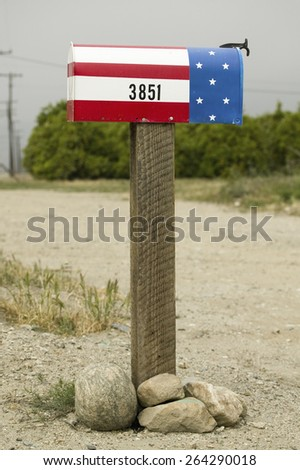 A red, white and blue patriotic U.S. mailbox standing along the roadside in Ventura County near Santa Paula, California. - stock photo