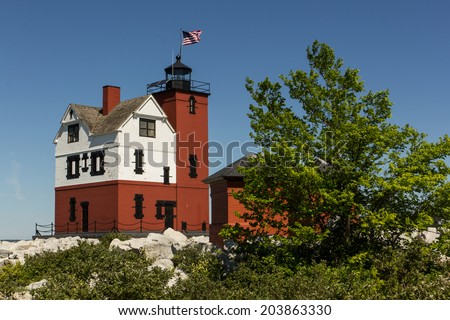 A red & white lighthouse on a rocky beach.  Round Island Lighthouse, Hiawatha National Forest, MI, USA. - stock photo