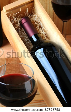 A red wine bottle in a wooden box filled with straw on a tasting room table with two glasses of poured wine. - stock photo