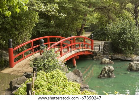 a red wooden bridge over a pond in a japanese garden
