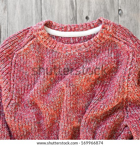 A red wool jumper on a wood surface - stock photo