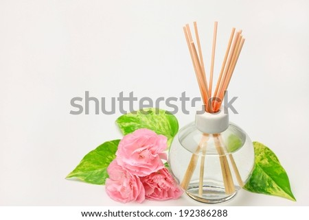 A reed diffuser with oil and reeds next to flowers and leaves. - stock photo