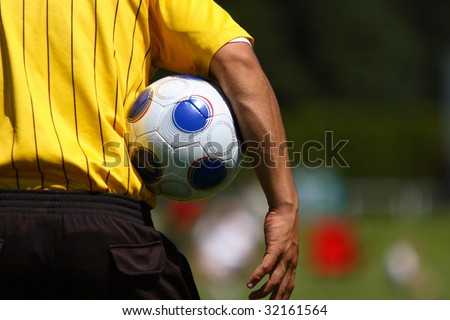 A referee with a soccer ball.