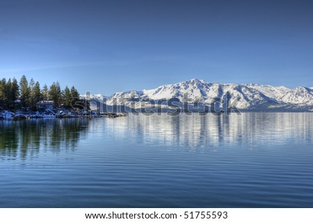 A reflection of Elk Point on Lake Tahoe from Marla Bay with Pyramid Peak and Mount Price reflecting in the background. - stock photo