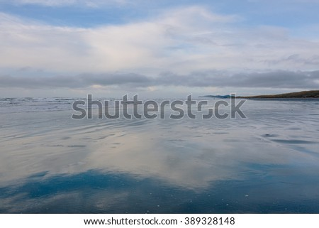A reflection of the sky in the peaceful Pacific Ocean along the beach
