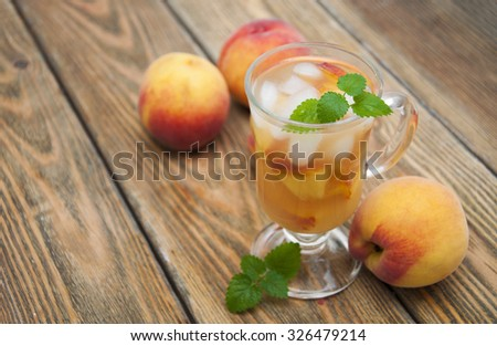 A refreshing cold drink with peach on a wooden table - stock photo