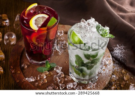 a refreshing summer drinks on a rural texture. authentic picture . mojito and sangria. focus on the surface of beverage - stock photo