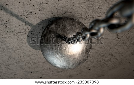 A regular metal wrecking ball attached to a chain hitting a concrete surface - stock photo