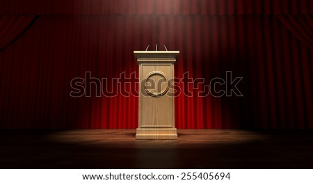 A regular theater stage with closed red curtains and a wooden debate podium lit by a single spotlight - stock photo