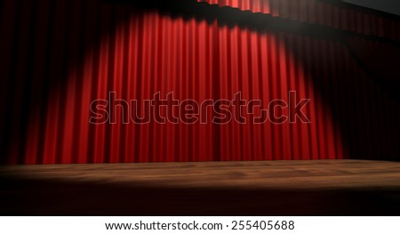 A regular theater stage with closed red curtains lit by a single spotlight - stock photo