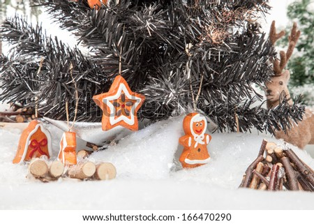 A Reindeer is watching trough a christmas Tree in a bright winter Scenery. - stock photo