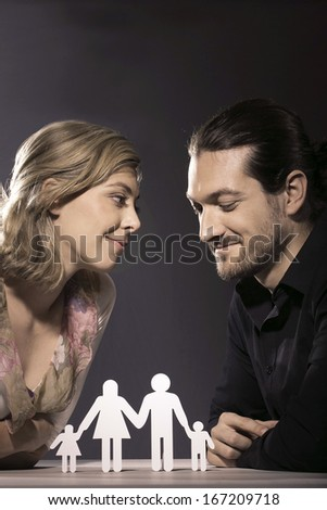 A relationship issue is being discussed by a couple at an intimate meeting. The woman gazes intently at the man who casts his gaze down to a paper cut out of a man, woman and two children. - stock photo