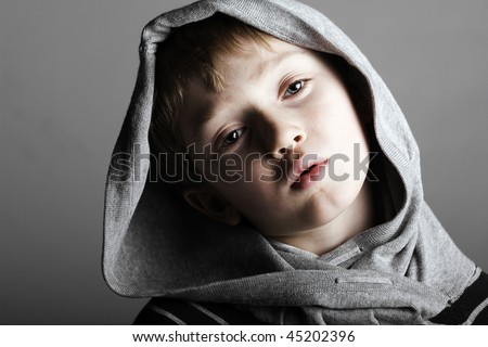 a relaxed little boy in a cool pose with a hoodie gazes on in a low key dramatic setting
