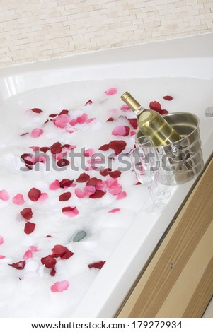 A relaxing bath with rose petals ,wine and glasses - stock photo