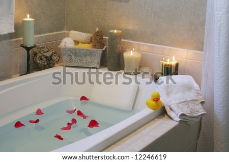 A relaxing candlelit bath with rose petals and a a rubber duck. Low lighting since bathroom was only lit with candles to create relaxing atmosphere. - stock photo