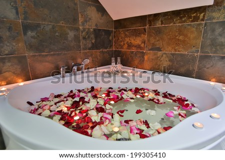 A relaxing candlelit bath with rose petals and a a rubber duck. Low lighting since bathroom was only lit with candles to create relaxing atmosphere - stock photo