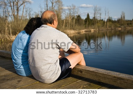 A relaxing senior asian couple sitting by the lake spending time together - stock photo