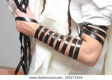 A religious orthodox Jew with arm-tefillin on his left hand prays A jewish man is preparing the tefillin - stock photo