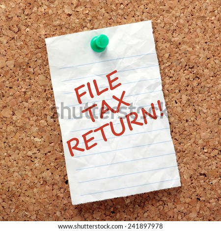 A reminder note to finish and file your tax return on a piece of crumpled, lined paper pinned to a cork notice board - stock photo