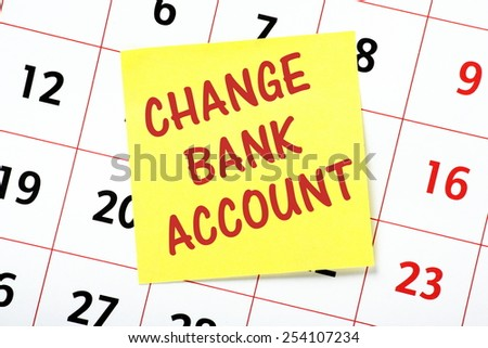 A reminder to Change Bank Account written in red ink on a yellow sticky note and pasted to a wall calendar - stock photo