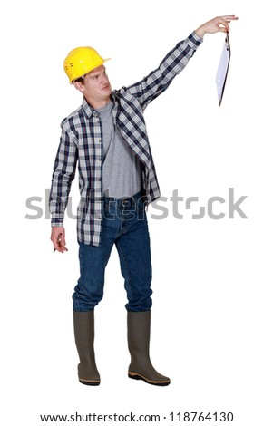 A repulsed tradesman dangling a clipboard - stock photo