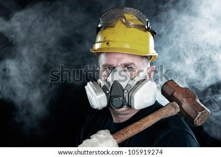 A rescue worker wears a respirator in a smokey, toxic atmosphere carrying a sledgehammer. - stock photo