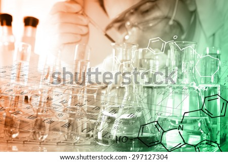 A researcher is analyzing sample in laboratory with periodic table and chemical equations background - stock photo