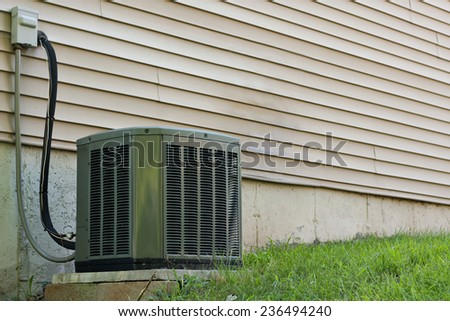 A residential central air conditioning unit sitting outside a home used for regulating the homes AC to a comfortable level. - stock photo