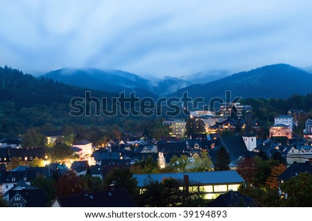 A residential community set in misty foothills. It looks to be morning, and there are no people viewable. Horizontally framed shot.