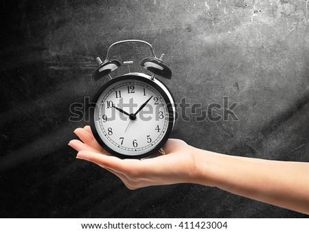 A retro alarm-clock on female hand, grey background - stock photo