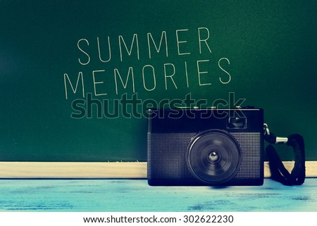 a retro camera on a rustic blue wooden surface and the text summer memories written on a green chalkboard, with a filter effect - stock photo