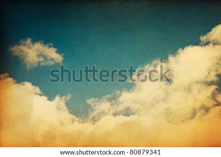 A retro cloudscape with vintage colors and a textured paper background. - stock photo