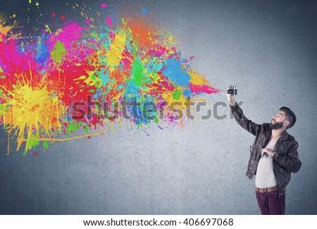 A retro hipster male taking photograph with a vintage camera of an urban wall with paint splatter concept