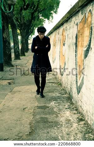 A retro styled girl walking down a rotten street along a graffiti sprayed wall in a urban environment. - stock photo