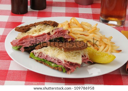 A Reuben sandwich on dark rye with french fries