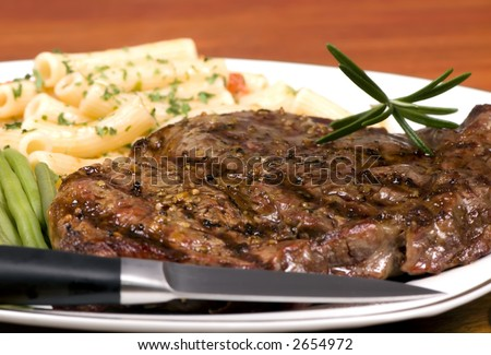 A rib Eye steak with pasta and vegetables - stock photo