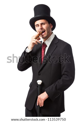 a rich businessman with a cigar wearing a top hat and carrying a walking stick - stock photo
