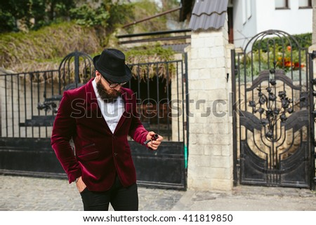 a rich man in a jacket near his house - stock photo
