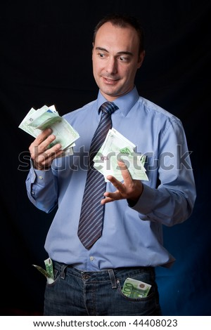A rich man shows his earnings with an expression of surprise. Wads of money in his hands and pockets. - stock photo