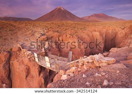 A rickety bridge over a narrow canyon with a volcano in the distance. Photographed at the foot of Volcan Licancabur in the Atacama Desert, northern Chile, at sunset. - stock photo