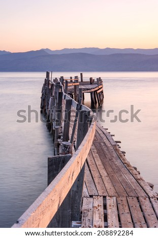 A rickety wooden jetty leading out from the beach into the Ionian sea on the Greek island of Corfu on a warm summer morning. - stock photo