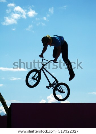 a rider performing air trick with clouds at the background