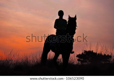 A Rider Silhouette on Horseback at sunset - stock photo