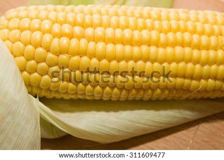 A ripe fruit of corn on a wooden surface