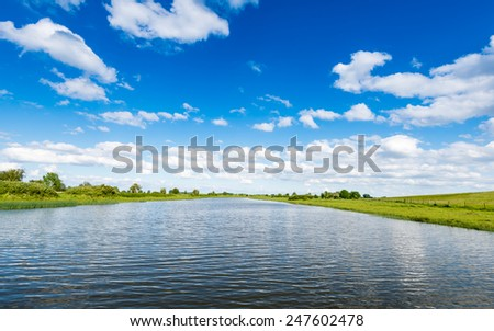 A rippling water surface and a blue sky with some white clouds on a hot summer day. - stock photo