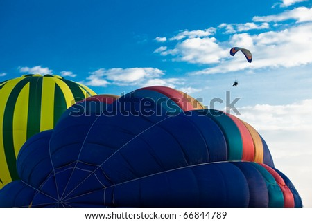 A rising balloons and a paramotor in the sky. - stock photo