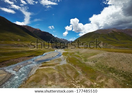 A river cross a plains in Tibetan Plateau, with mountain landscape and cloudy sky