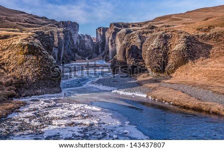 A river flows and cuts through an ancient gorge in Iceland.